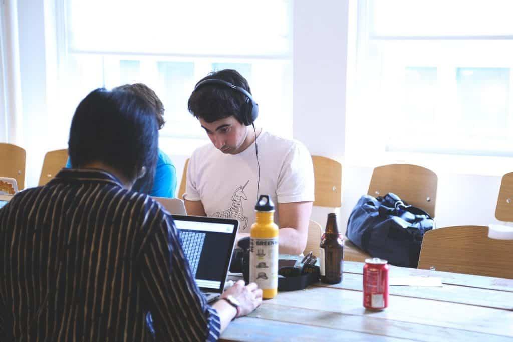 Imagem mostra pessoas em uma mesa trabalhando em notebooks.