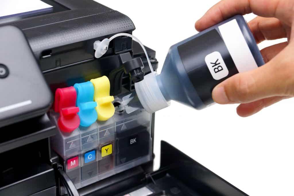 Imagem de pessoa reabastecendo cartucho de impressora com tinta preta