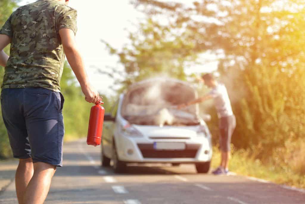 Um homem com extintor ABC nas mãos. Ele está de frente para um carro com fumaça saindo no motor. Ao lado do carro existe uma mulher. Tudo acontece em uma estrada.