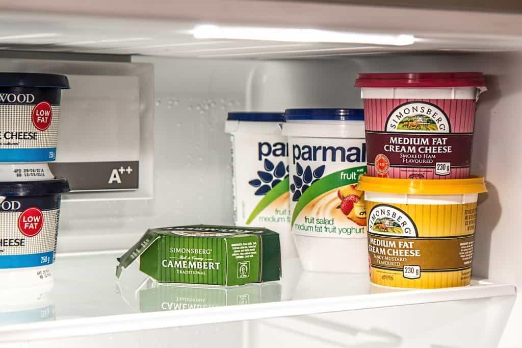Na foto uma prateleira de geladeira com queijos e iogurtes dentro.