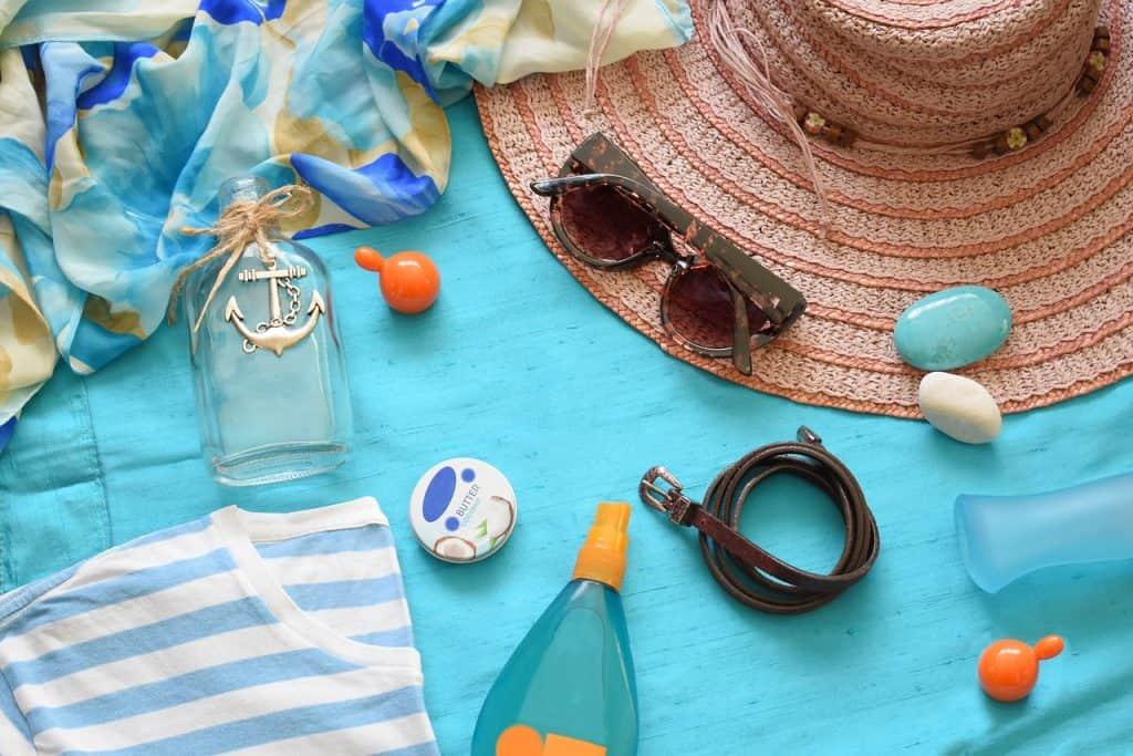 Imagem de hidratante pós-sol junto com artigos de praia.