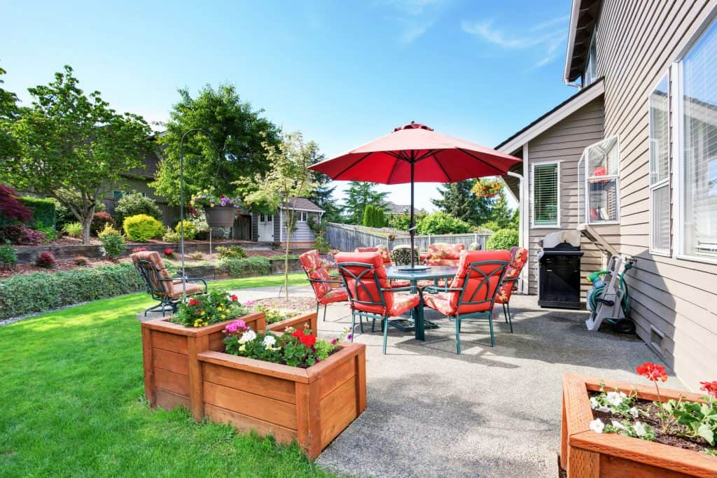 Imagem de jardim nos fundos de uma casa com ombrelone.