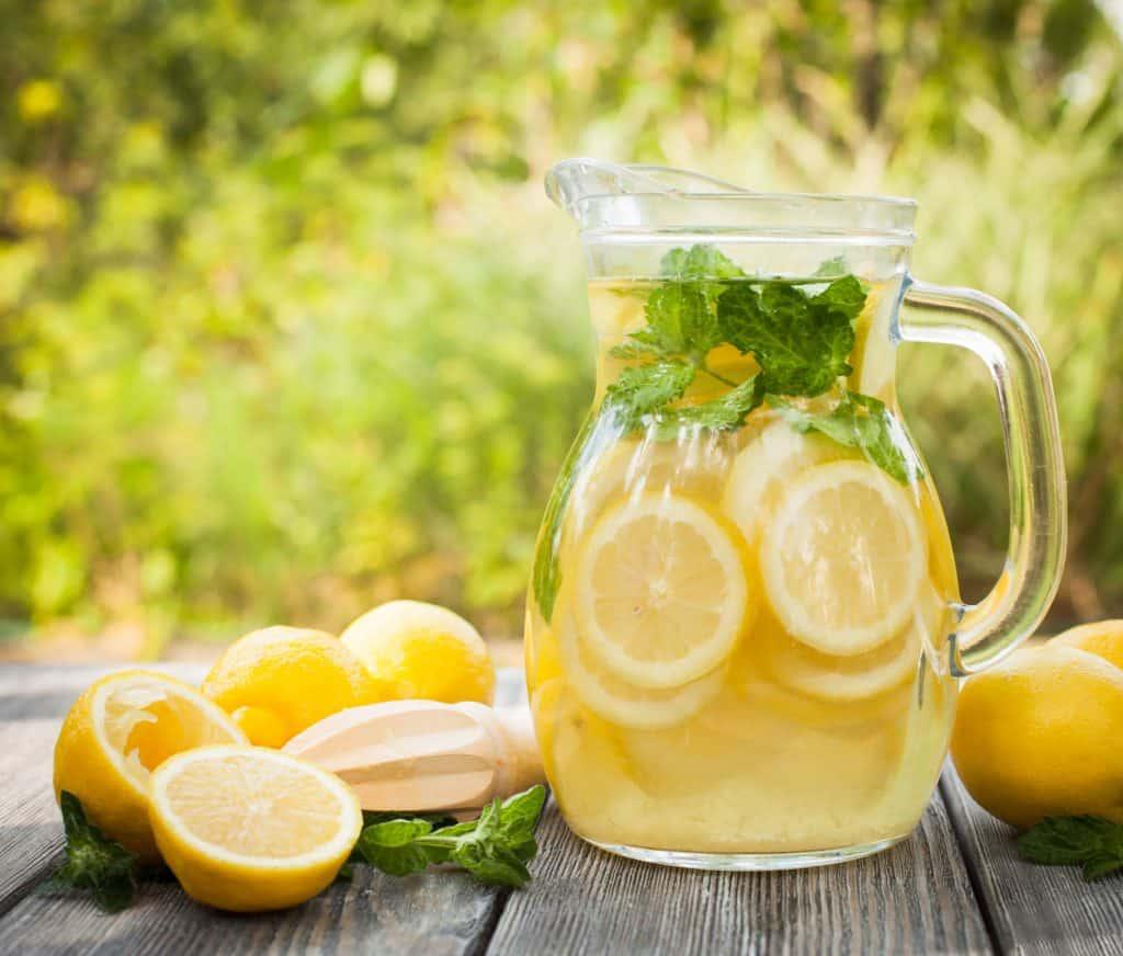 Imagem de jarra com suco de limão e limões ao lado.