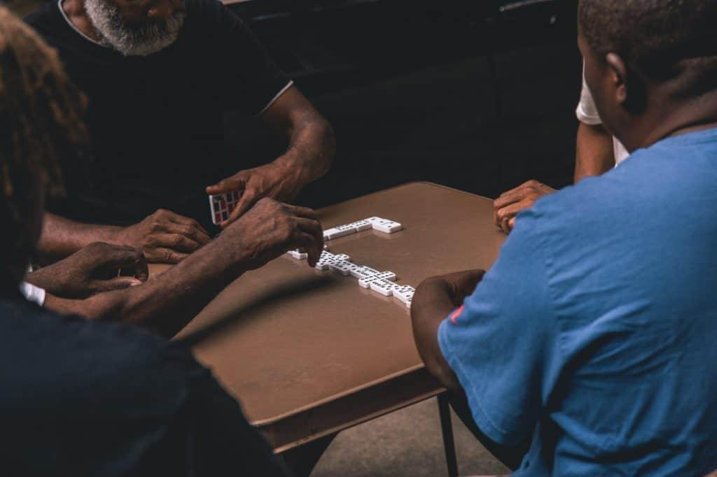 Imagem mostra o momento de um jogo de dominó, com quatro participantes e mais uma pessoa observando, em primeiro plano.