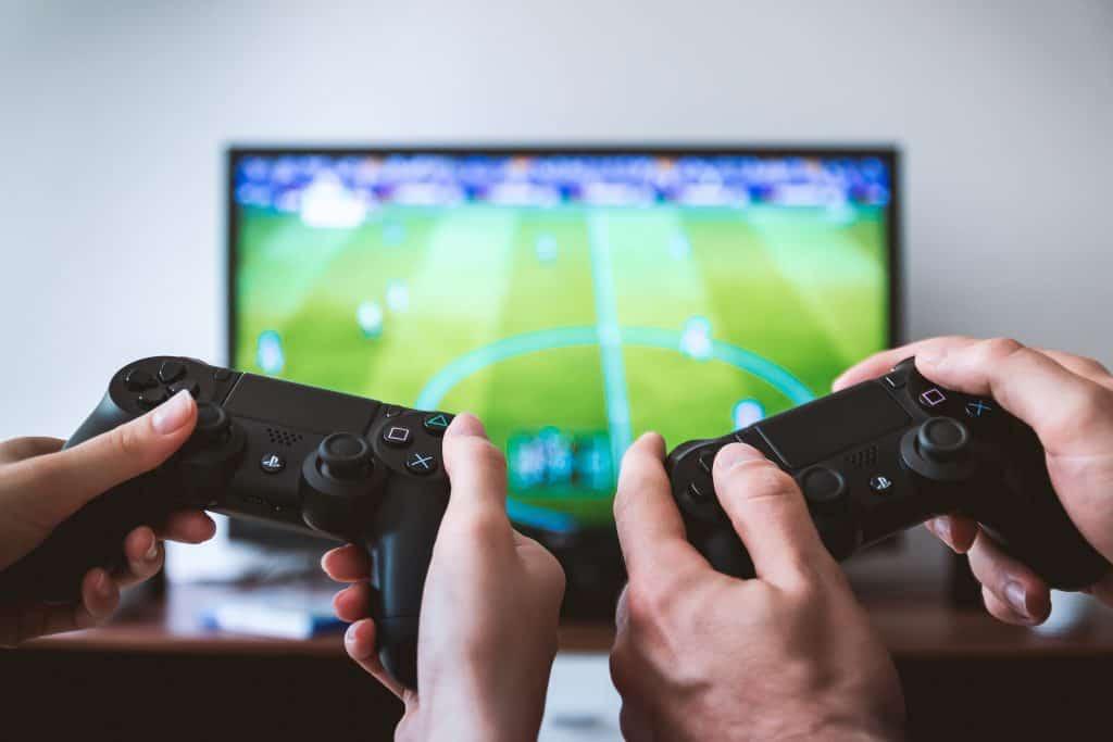 Na foto as mãos de duas pessoas segurando controles de videogame e uma televisão ao fundo com um jogo de futebol.