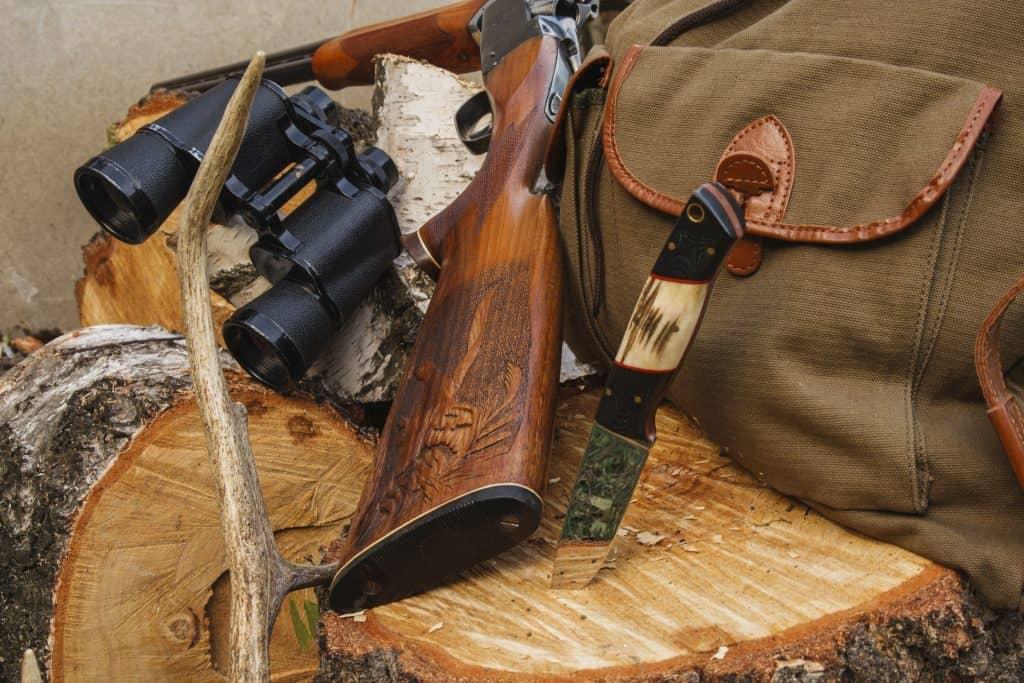 Uma faca de caça fincada em um tronco de madeira ao lado de uma espingarda e mochila.