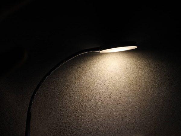 Foto de uma luminária simples, preta, com a lâmpada acesa, encostada em uma parede de um lugar escuro. Na parede, o feixe de luz provocado pela luminária.