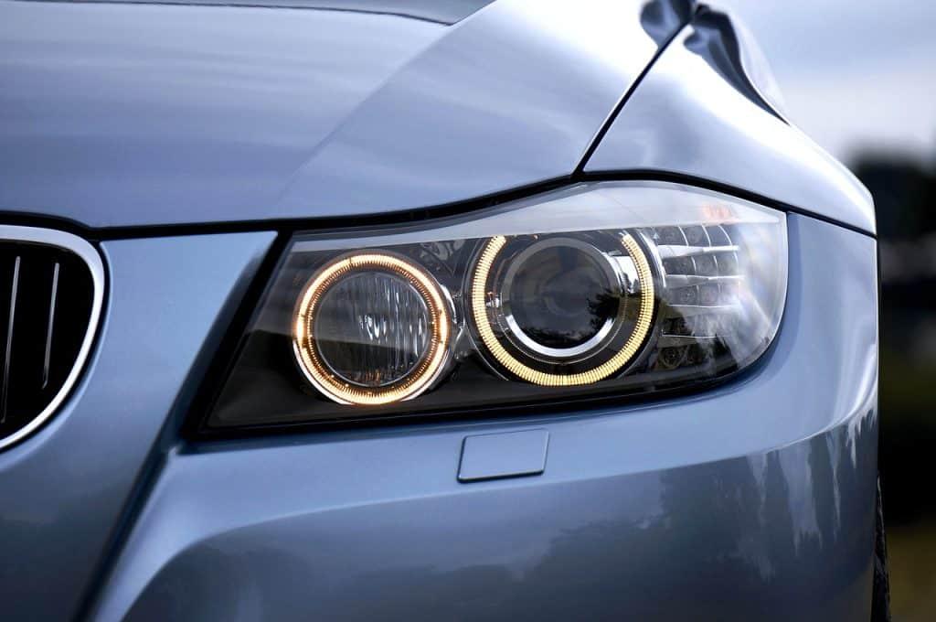 Imagem de carro BMW com faróis de lâmpada xenon em destaque.