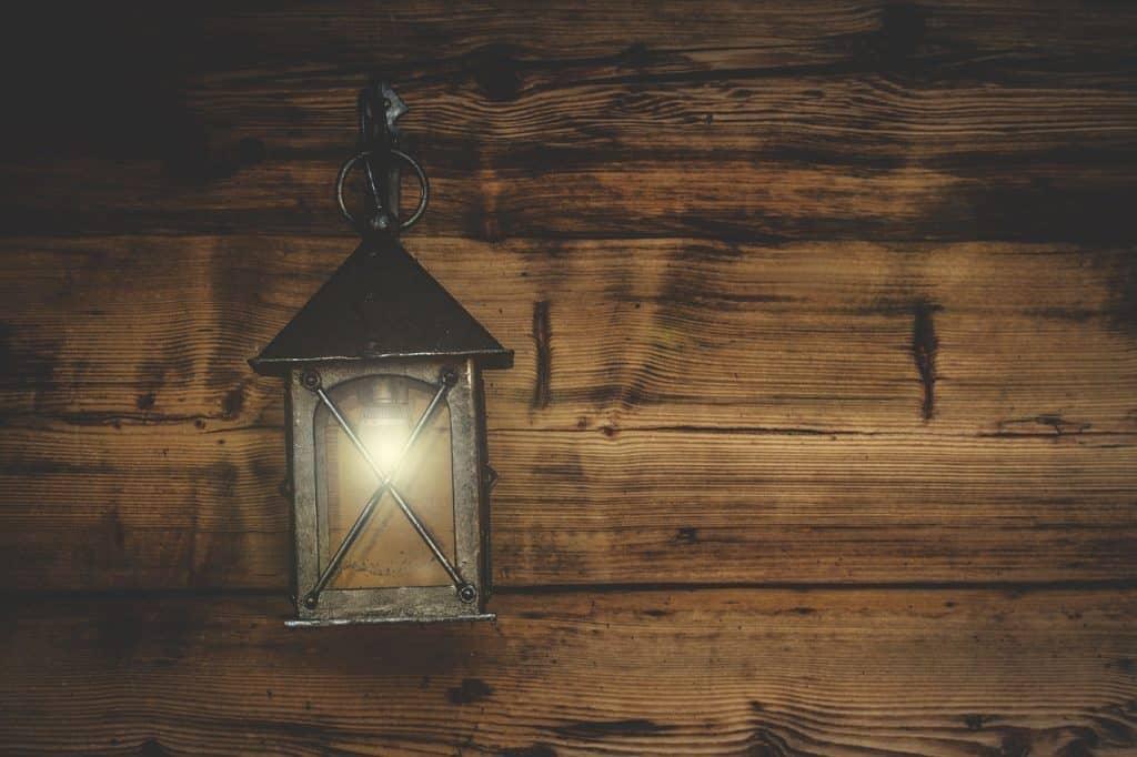 Imagem de lampião de LED de metal pendurado em parede de madeira.