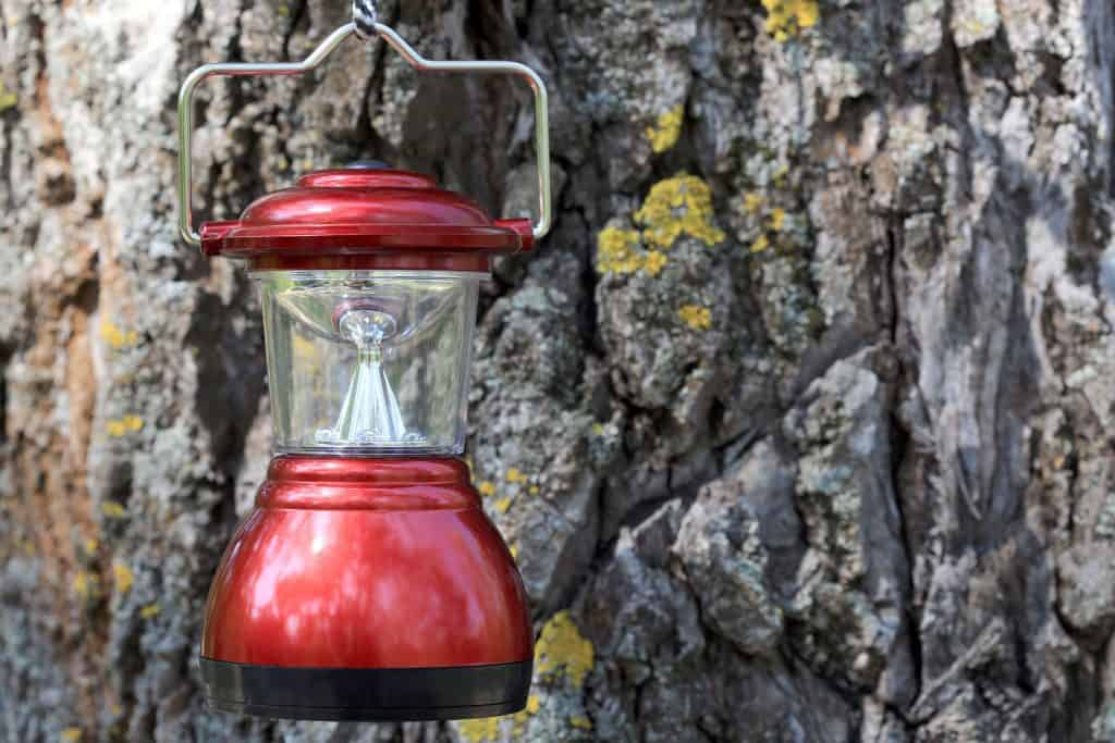 Lampião de LED pendurado na frente de um tronco da árvore.