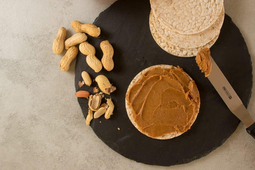 Imagem de amendoins e pasta de amendoim sobre pão de amendoim.