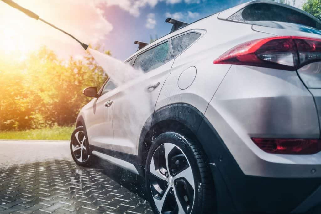 Imagem mostra lavadora de alta pressão lavando lateral de um carro cinza.
