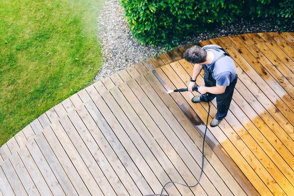 Imagem mostra um homem usando lavadora de alta pressão para limpar deck.