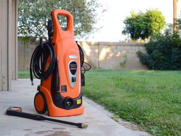 Imagem mostra uma lavadora de alta pressão na área externa de uma casa.