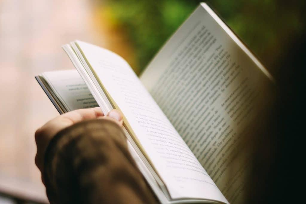 Destaque de mão com livro aberto.