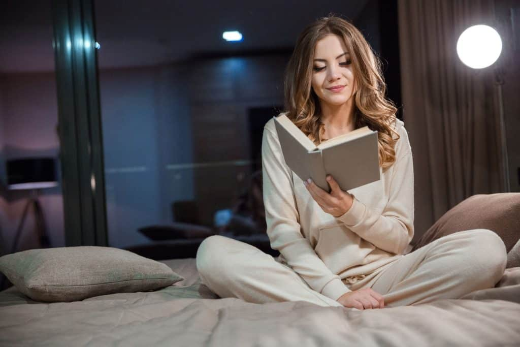 Imagem de mulher lendo com lâmpada de leitura ao fundo.