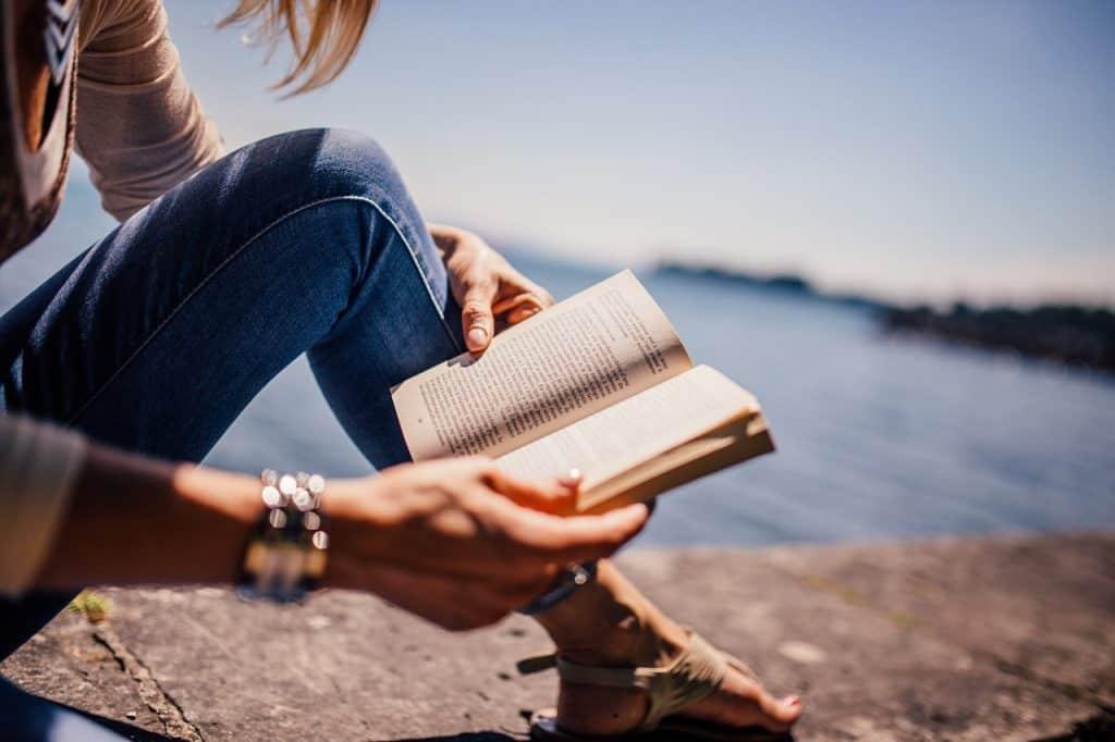 Mulher sentada no chão, lendo livro com mar ao fundo.