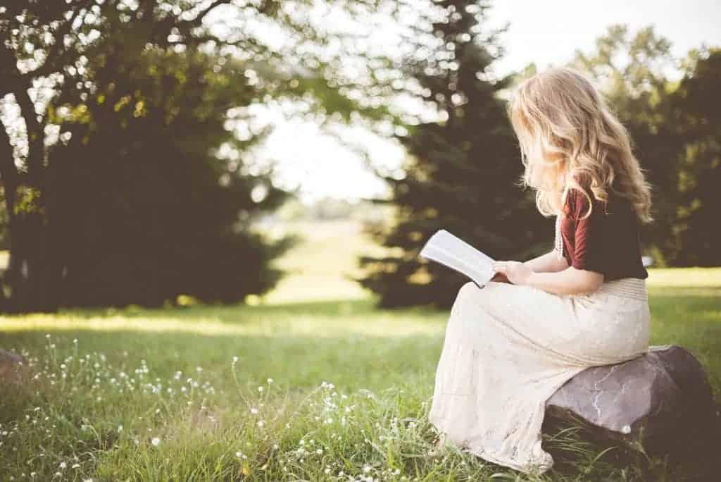 Imagem de mulher sentada lendo um livro em um jardim.
