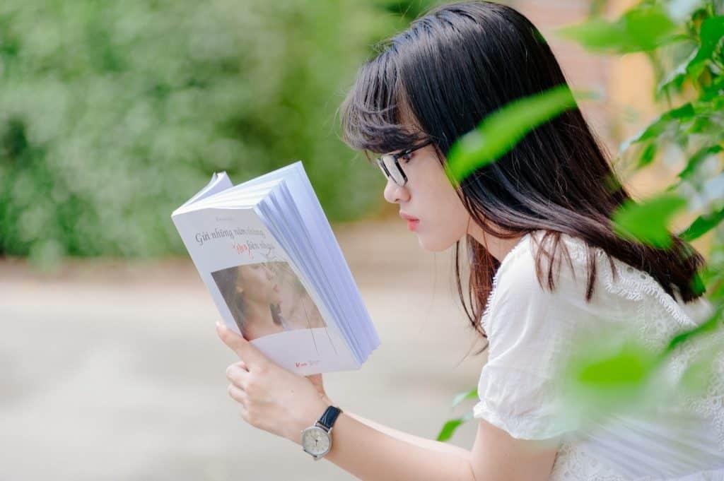 Menina lendo livro ao ar livre.