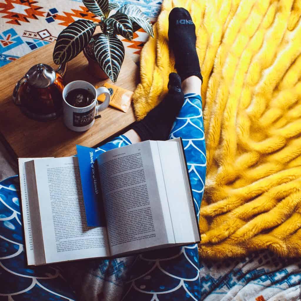 Um livro aberto com um marcador de página dentro dele. O livro está sobre as pernas de uma pessoa em cima de uma cama. Estão presentes no quadro uma coberta, uma bandeja de madeira de café-da-manhã, uma caneca, uma chaleira, um pacote de chá e um pequeno vaso com planta.