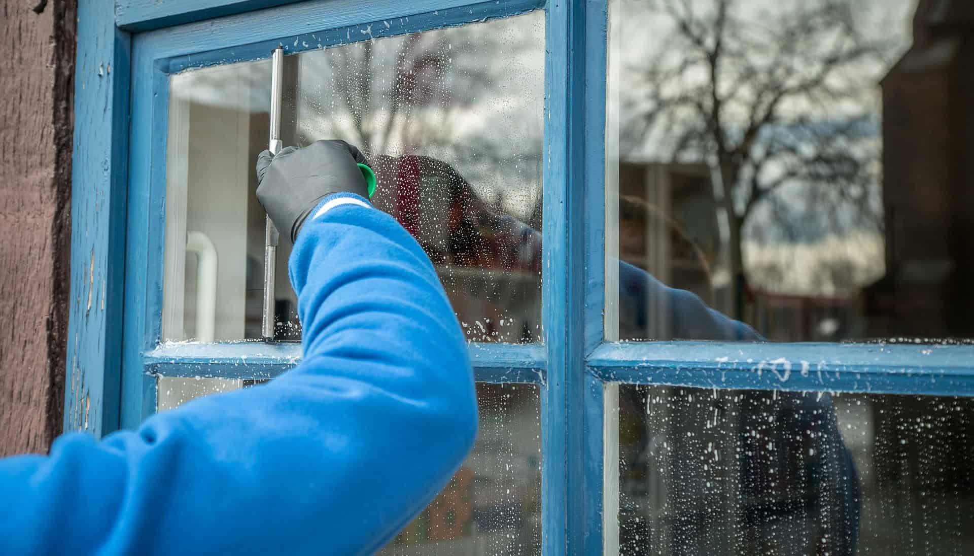 Imagem mostra braço de uma pessoa limpando janela pelo lado externo com auxílio de rodo pequeno.