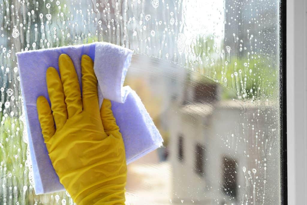 Imagem mostra mão com luva amarela limpando vidro com pano.