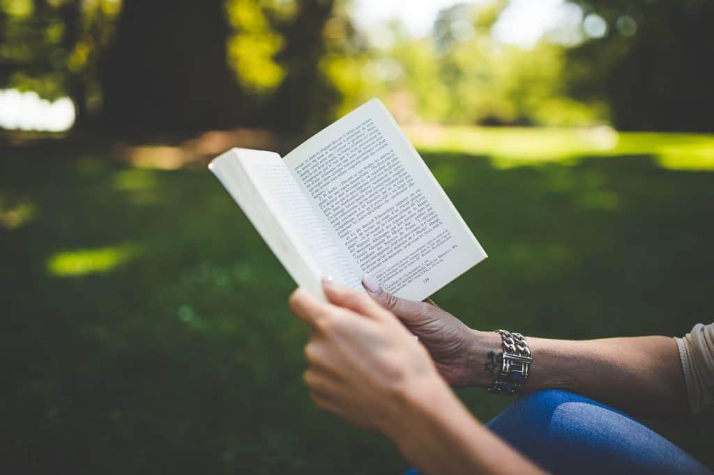 Pessoa lendo um livro no parque.