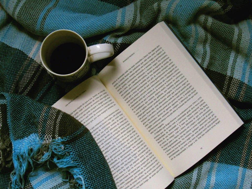 Livro aberto sobre manta xadrez, com caneca de café ao lado.