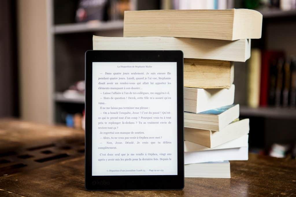 Kindle com livros ao fundo.