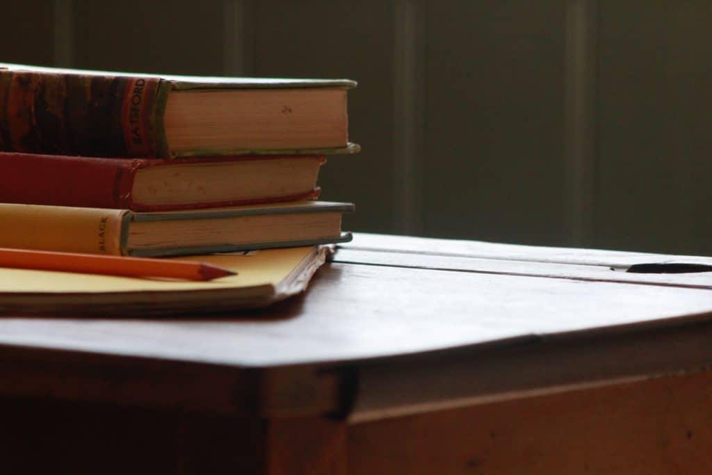 Imagem de livros empilhados sobre mesa.