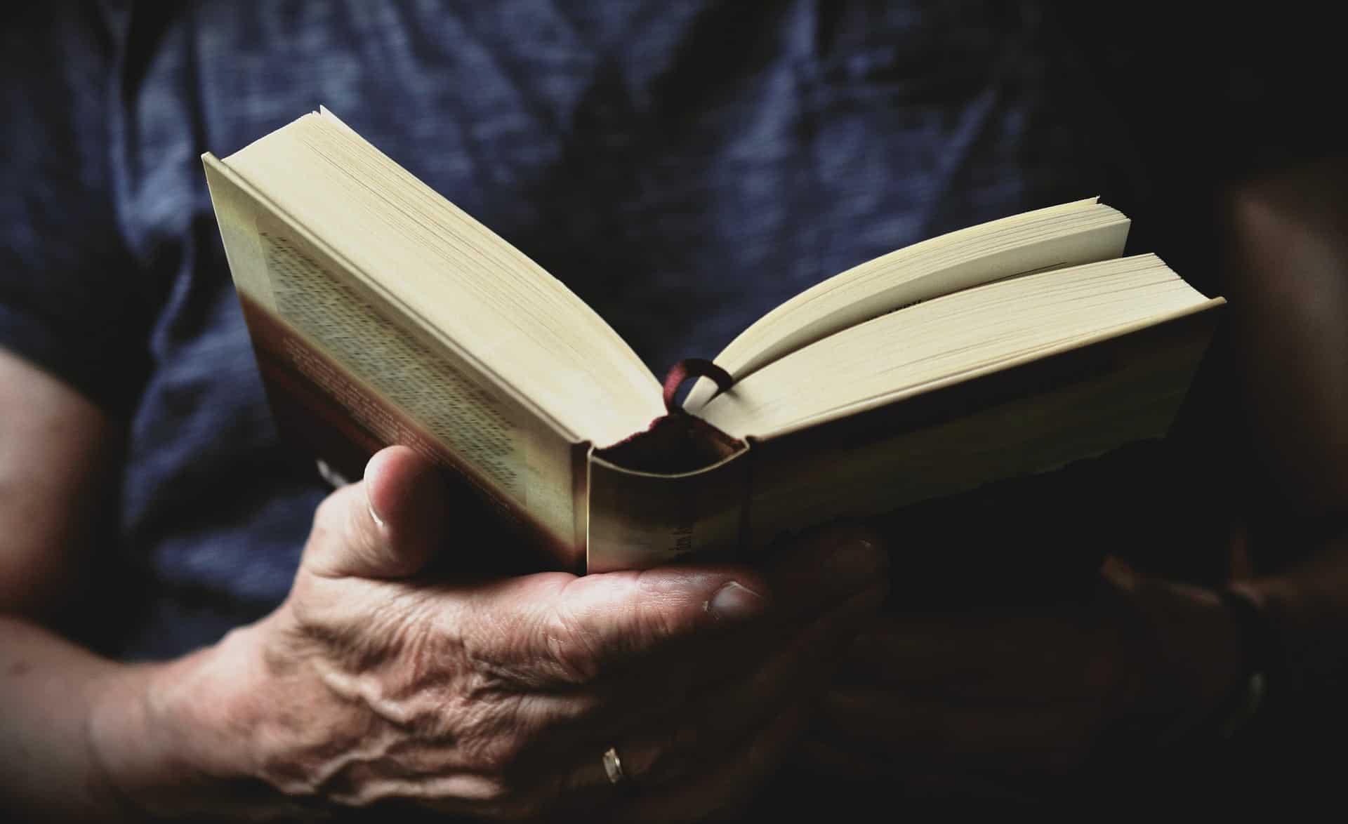 Destaque de mãos de homem segurando livro aberto.