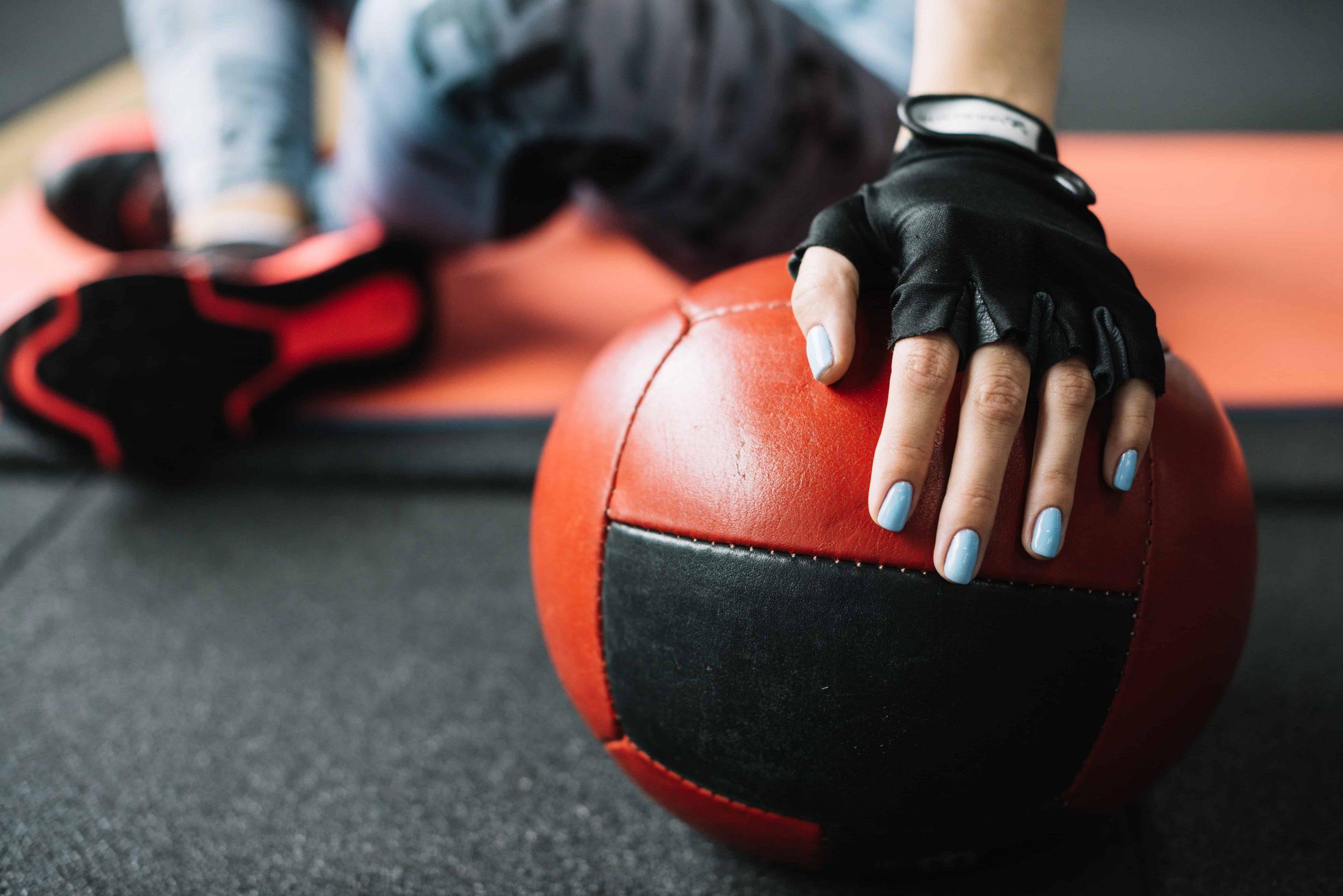 Moça sentada em colchonete de academia usando luvas esportivas pretas apoia mão sobre bola de couro.