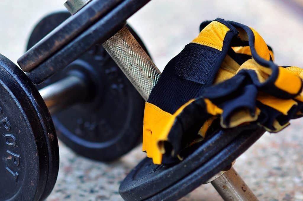 Par de luvas esportivas pretas com amarelo sobre par de halteres em metal.