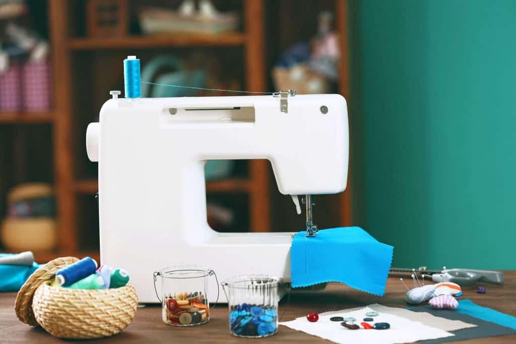 Máquina de costura sobre mesa, com tecidos, linhas e botões.