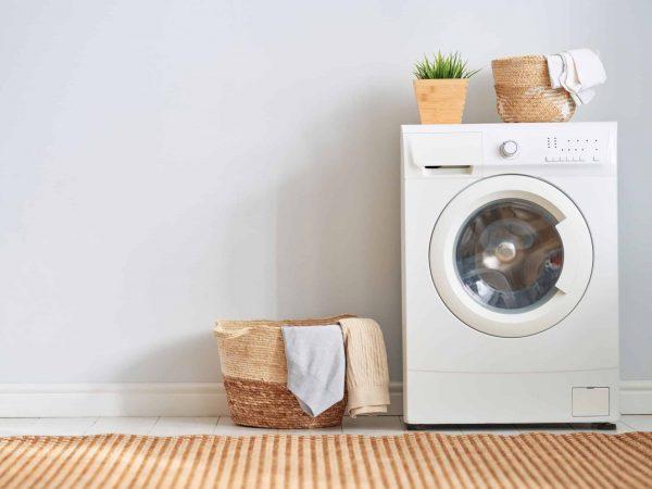 Imagem de máquina de lavar branca com cesto de roupas ao lado.