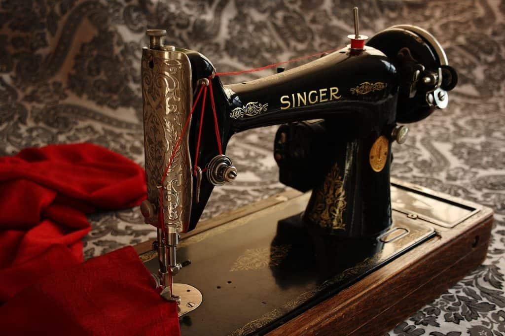 Máquina de costura Singer Pretinha, costurando tecido vermelho.