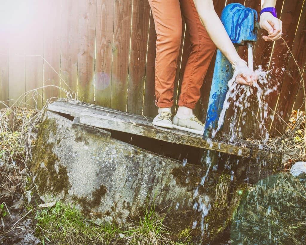 Imagem mostra uma pessoa com a mão em água de poço artesiano.