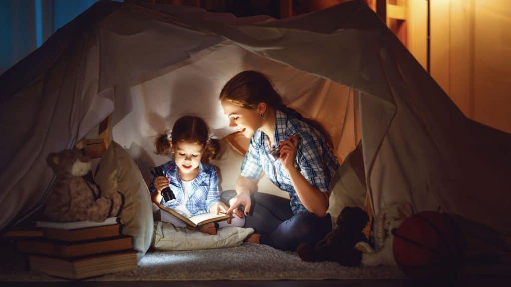 Na foto duas meninas dentro de uma cabana lendo um livro segurando lanternas.