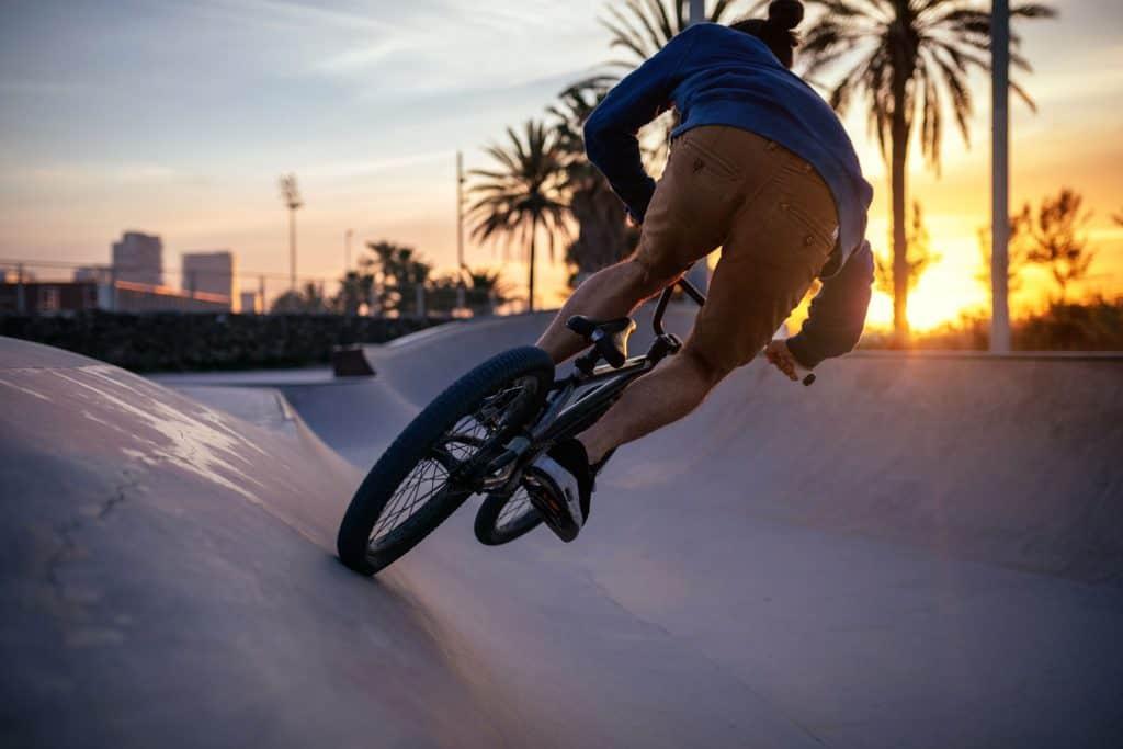 Imagem de pessoa em rampa de bicicleta com por do sol ao fundo.