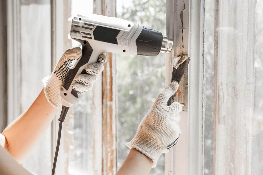 Imagem mostra mãos segurando soprador térmico e espátula para reparo em uma janela.