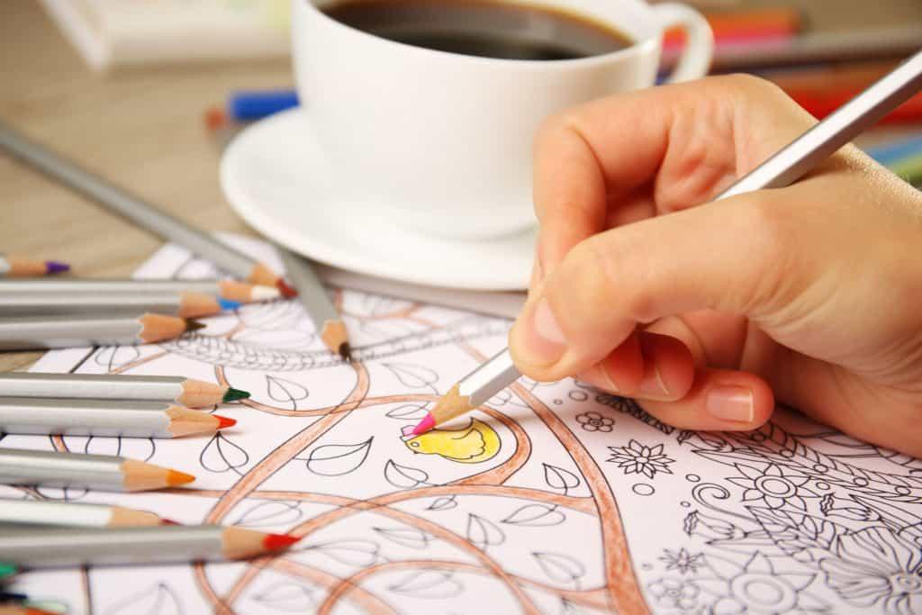 Foto que mostra uma mão de um adulto pintando um livro de colorir com uma xícara de café e lápis de cor ao lado.