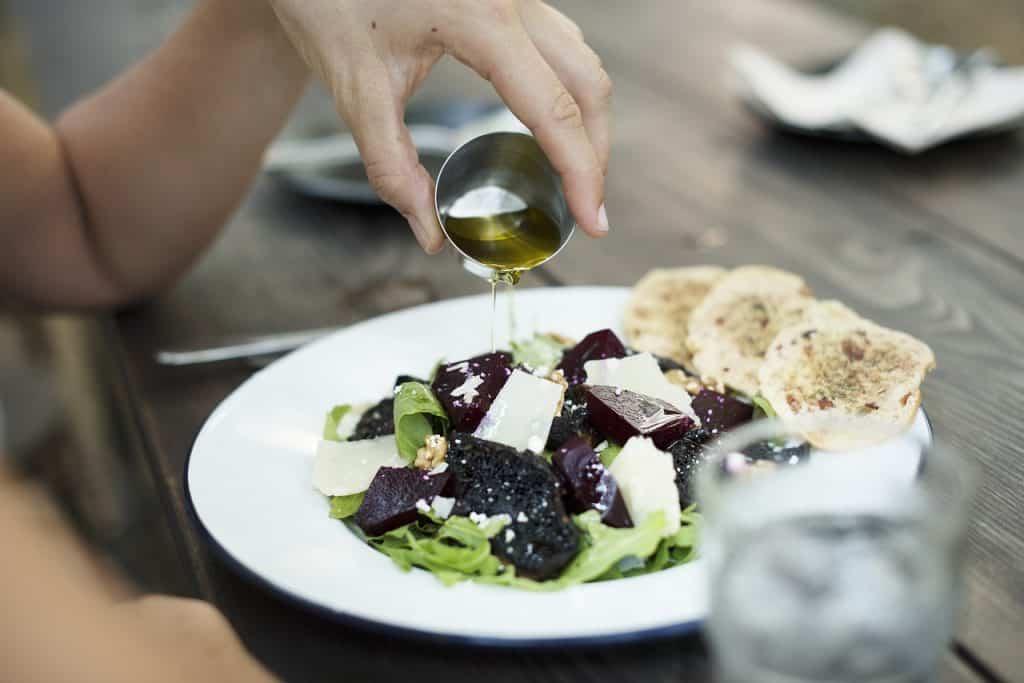 Mão colocando óleo sobre salada.