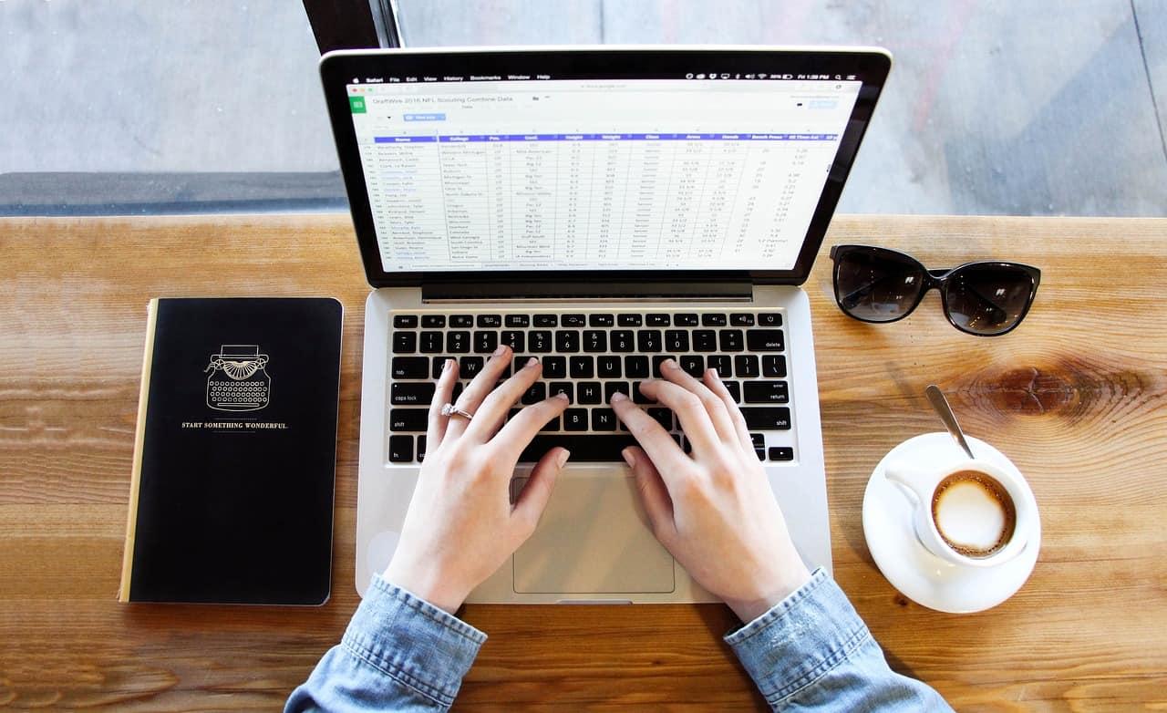 Imagem das mãos de uma mulher digitando em um notebook apoiado sobre mesa de madeira com um par de óculos escuros, uma caderneta de anotações e uma xícara de café ao lado.