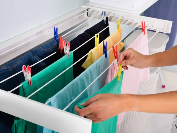 Imagem de mulher estendendo roupas em varal recolhível