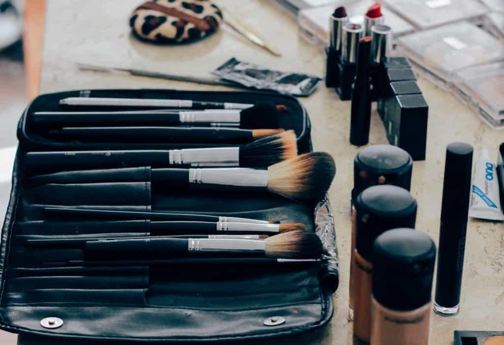 Foto de uma superfície com um estojo de pincéis de maquiagem, algumas bases líquidas, batons e outras makes.