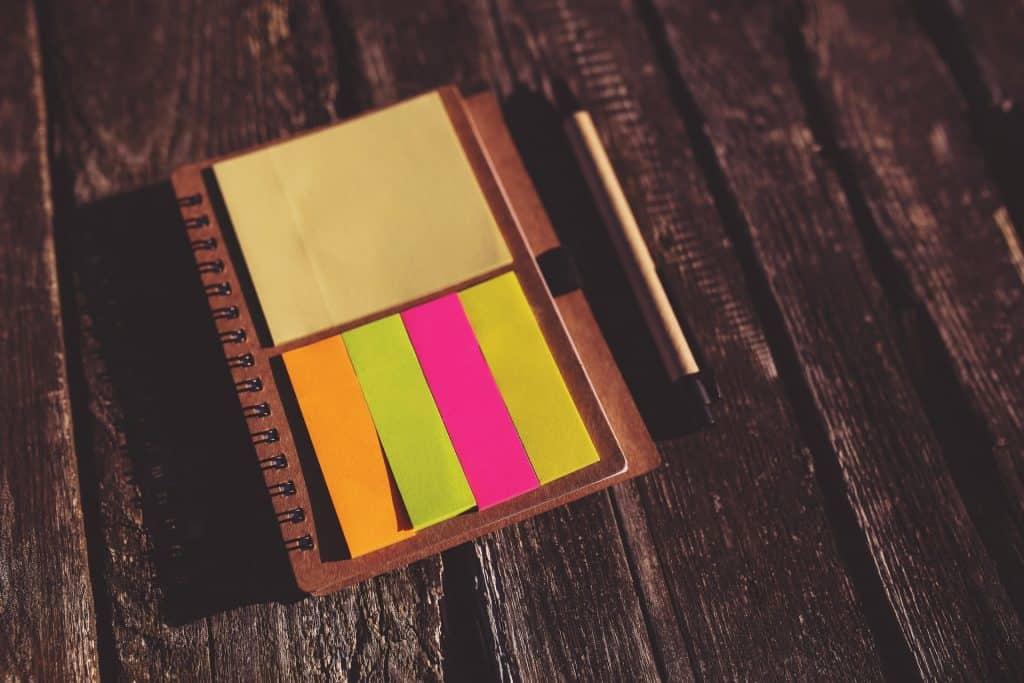 Um caderno com dois blocos, um de anotação tradicional e outro de marcadores de página em quatro cores diferentes. Ao lado do caderno está uma lapiseira e ambos estão sobre uma superfície de madeira.