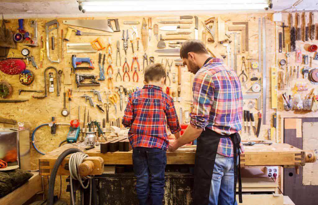 Imagem mostra um homem e uma criança em frente a uma mesa com ferramentas de marcenaria.