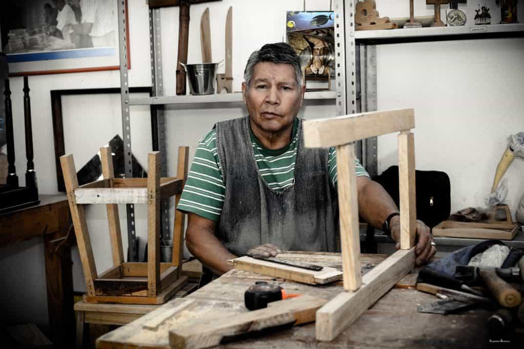 Imagem mostra um carpinteiro em sua oficina, com sua mesa repleta de ferramentas.
