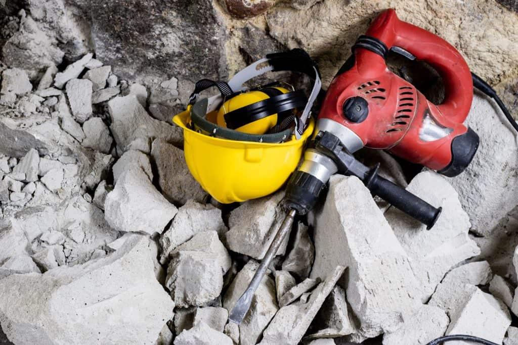 Imagem de martelo elétrico com obra demolida.