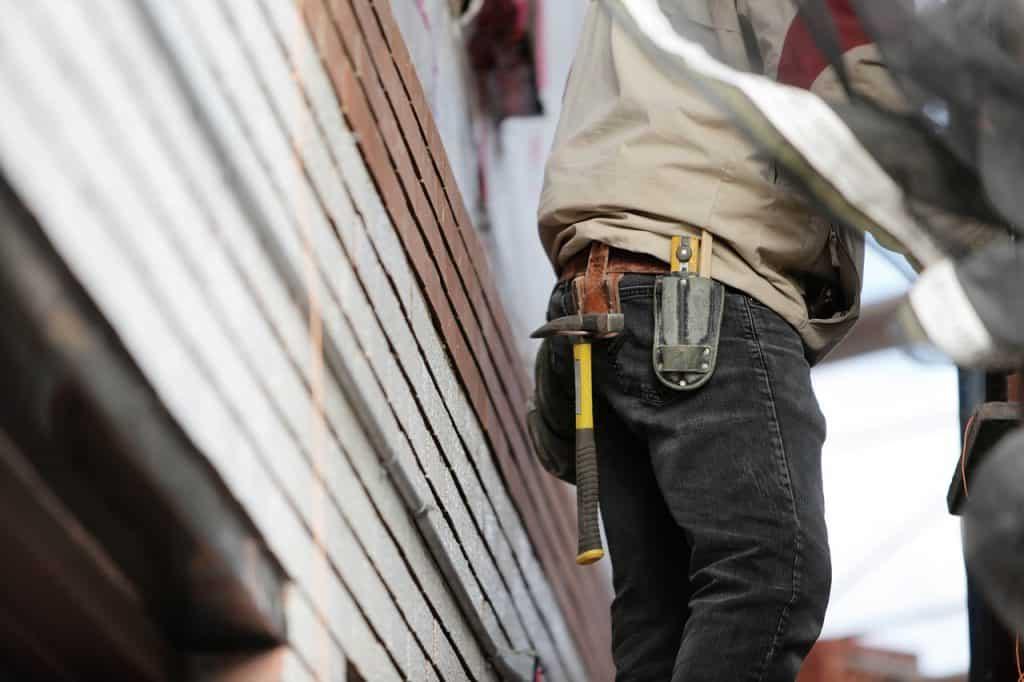 Foto de homem com cinta de ferramentas e martelo pendurado.